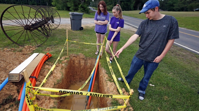 siblings stand around a fiber-optic line
