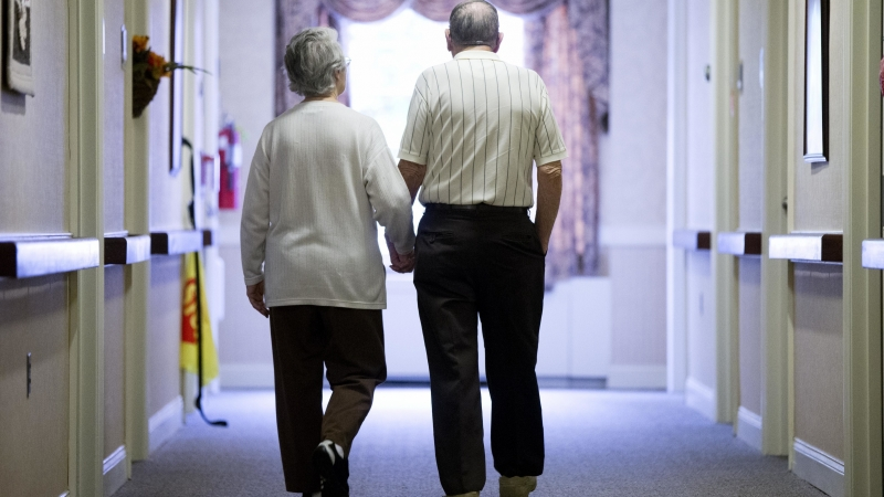 elderly couple walks down a hall of a nursing home
