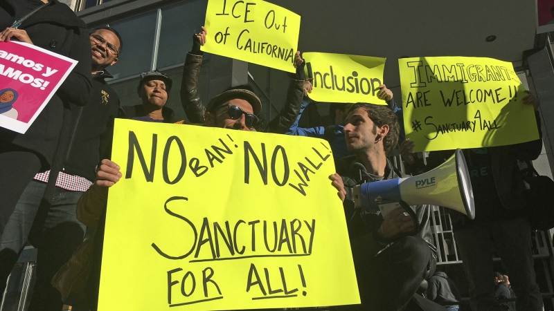 """Protesters hold up bright yellow signs reading """"No ban! No wall! Sanctuary for all!"""", """"I.C.E. Out of California,"""" and """"Inclusion."""""""