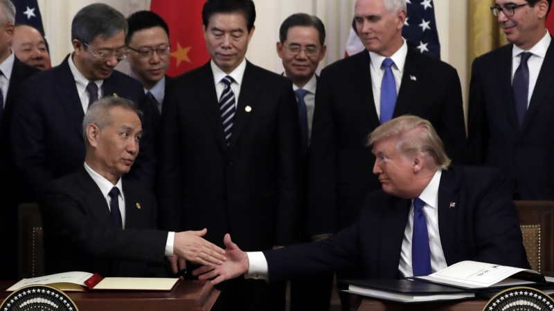 On left, Vice Premier Liu He reaches out to shake hands with President Donald Trump, on right. Behind them stand several men, including Vice President Mike Pence.
