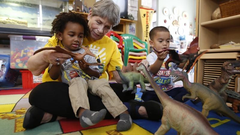 Child care provider Pat Alexander helps children