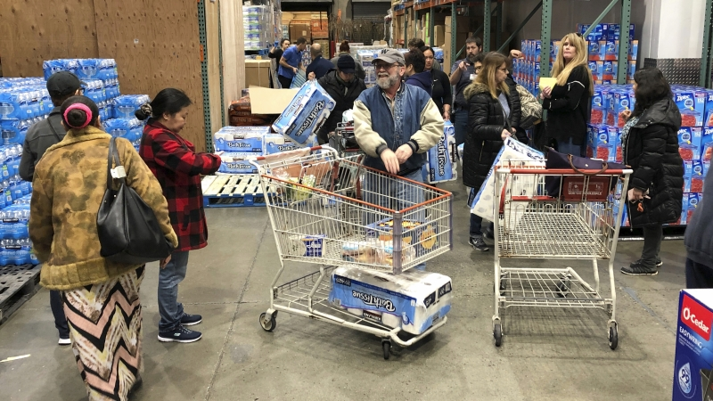Shoppers wait their turns to pick up toilet paper that had just arrived at a Costco store