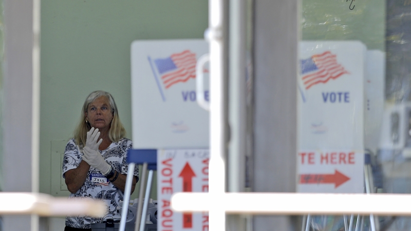 A polling place worker adjusts gloves