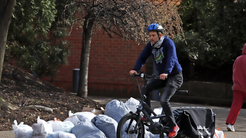 A bicyclist passes trash bags piled on the curb