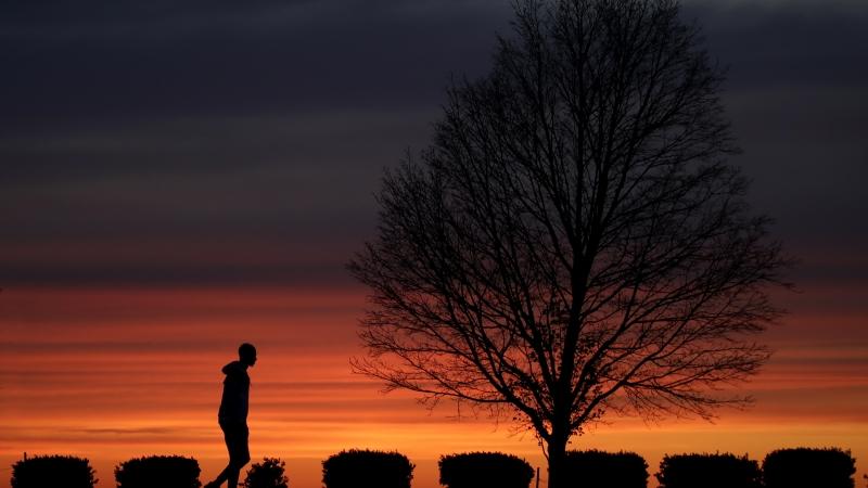 A man walks alone in a Kansas City, Mo., park at sunset