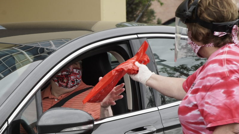 Kathy Zywiec hands out a bag containing employment information, during a drive-thru jobs fair in Omaha, Neb
