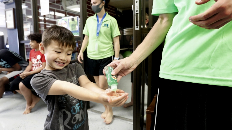 Bruce McCall, 5, smiles as he takes hand sanitizer during martial arts daycare summer camp