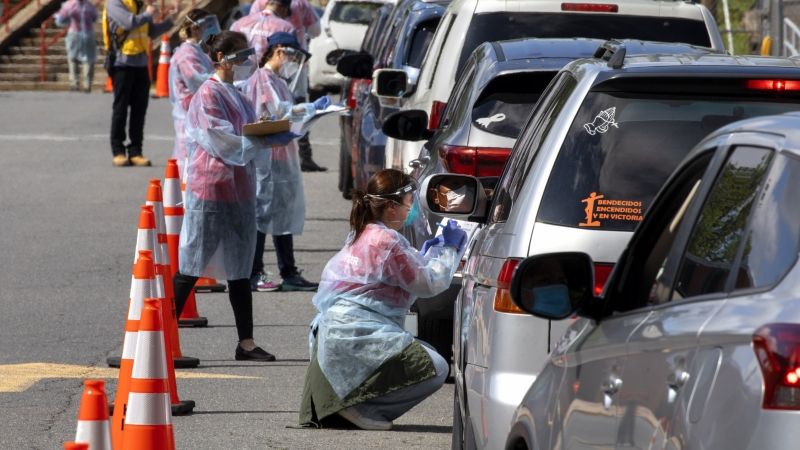 A man wearing a facemask waits inside his car to be tested for COVID-19