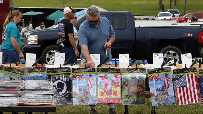 A man looks at items on a vendor's table at a flea market in Farmington, Pa.