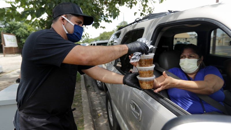 A man hands out containers of gumbo to a furloughed worker.