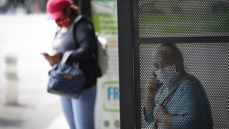 Two women wait at a bus stop amid the coronavirus pandemic