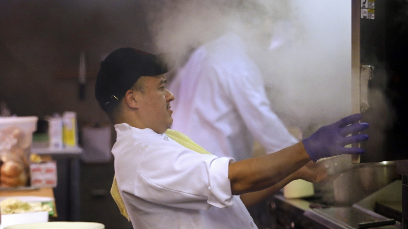 Arturo Ramirez backs away from a cloud of steam escaping from a steamer