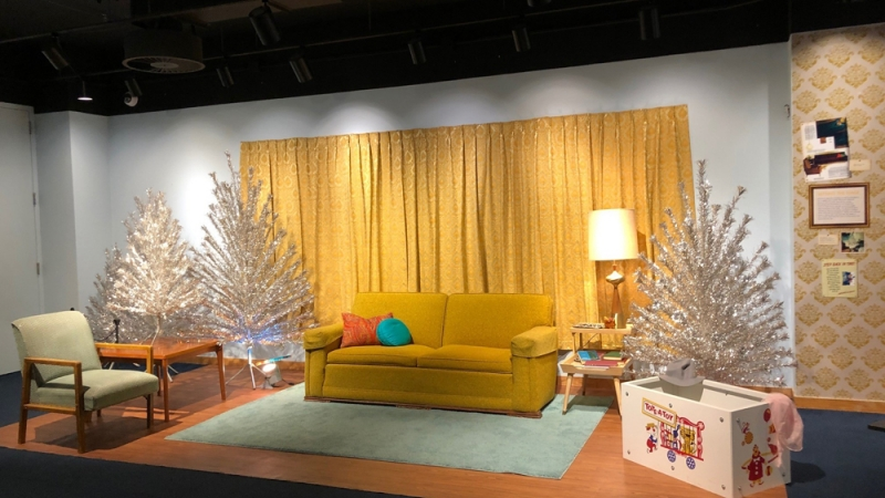 A 1960s-style living room is adorned with aluminum Christmas trees