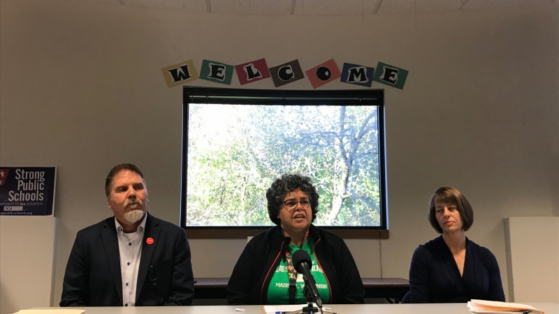 Three people sit at a table with a sign that says WELCOME over their heads. Sandra Rivera sits flanked by her union president and her lawyer.