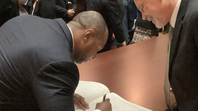 Jarrett Adams signs his name into the attorney book