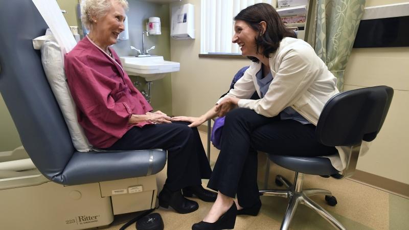 Dr. Allison Magnuson, left, speaks with patient Nancy Simpson