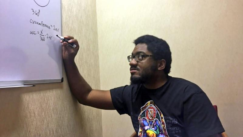 Shareef Jackson writes on a dry-erase board in a classroom