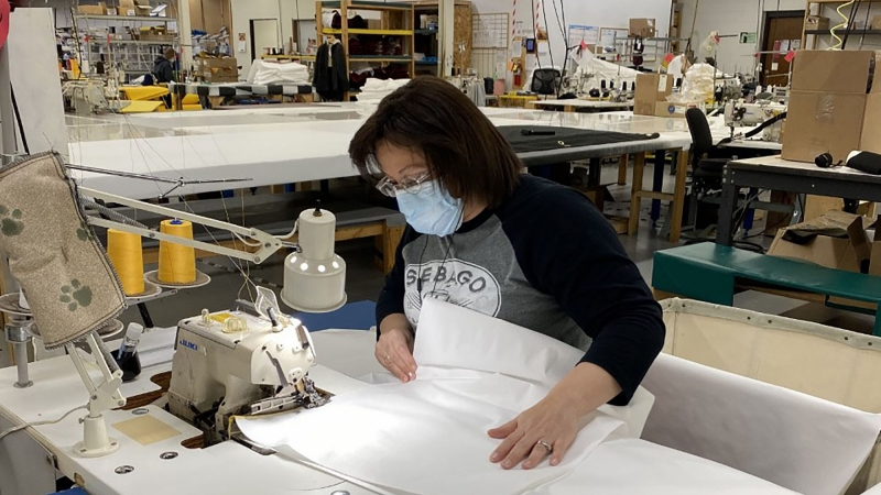 Stormy Kromer employee Penny Linnemanstons sews gowns that are being produced for health care workers