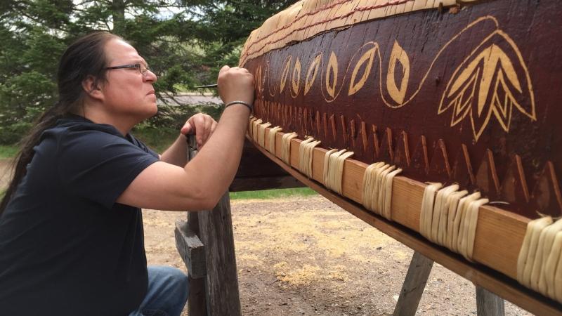 Wayne Valliere adds detail to a birchbark canoe he built