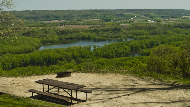 A picnic table and firepit of a campsite sit in the foreground with river and green treetops stretching in the background.