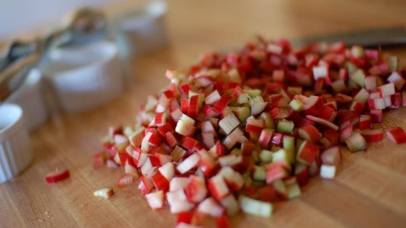 A pile of chopped rhubarb sits on a cutting board.
