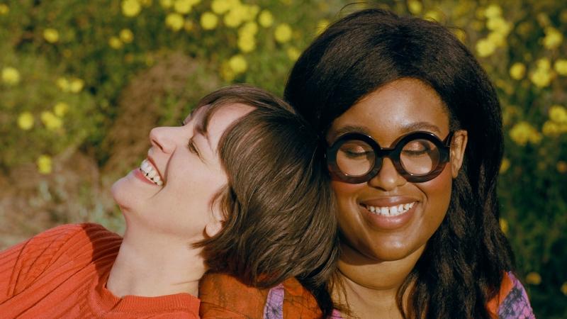 Ann Friedan (l) leans on friend Aminatou Sow in a green space.