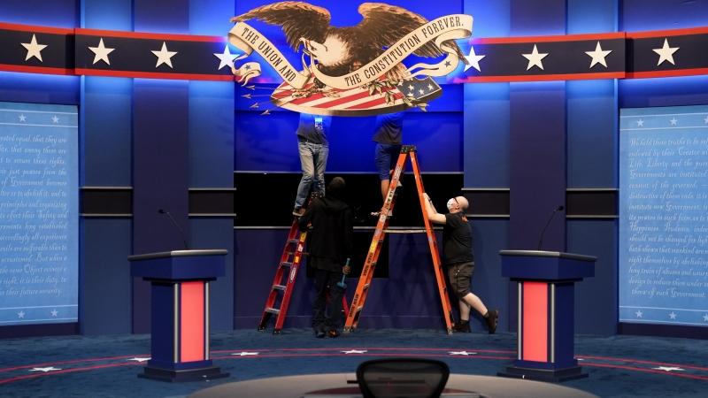 Workers adjusting signs on stage
