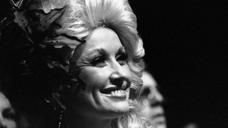 A black-and-white photograph of Dolly Parton in 1977
