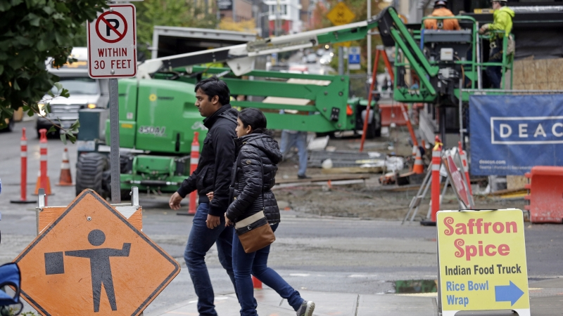 Pedestrians walk past a construction site near Amazon's South Lake Union headquarters in Seattle