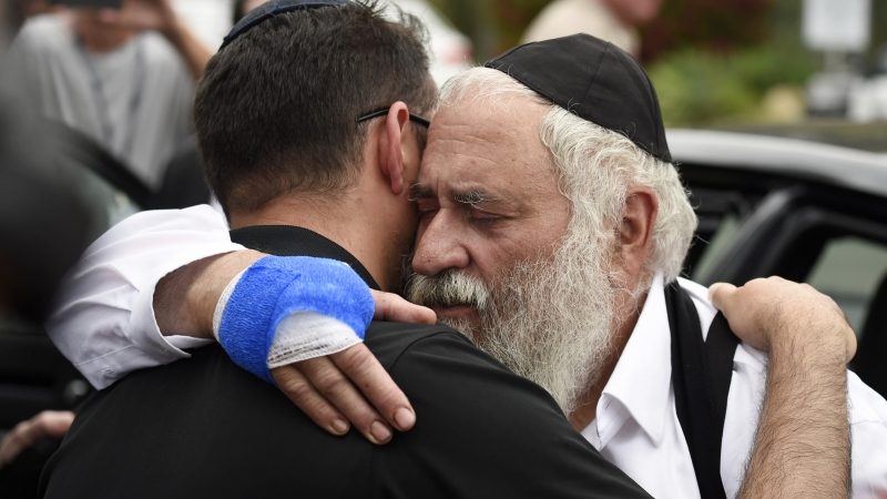 Man is hugged as he leaves a news conference at the Chabad of Poway synagogue
