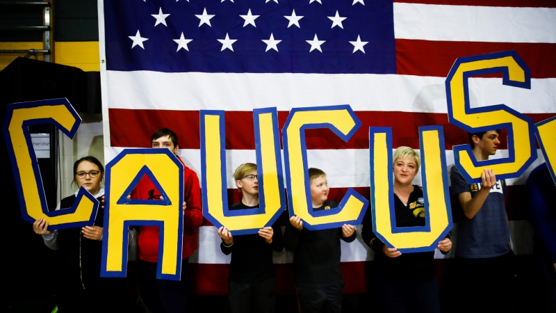 """Attendees spell out """"CAUCUS"""" during a campaign event"""
