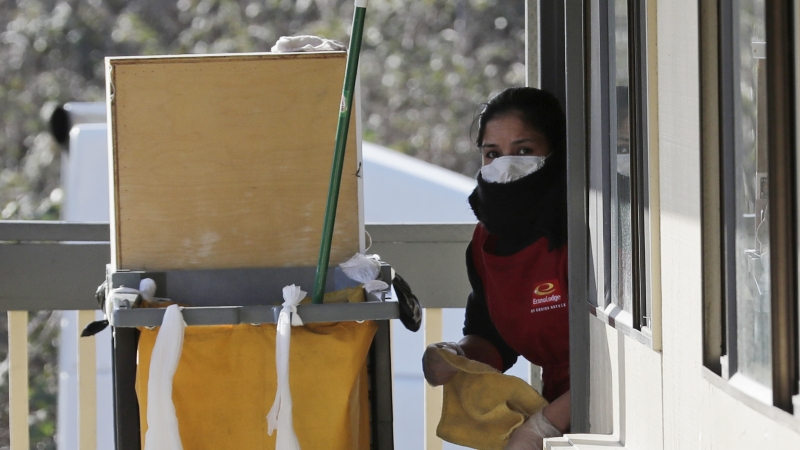 A housekeeping worker wears a mask as she cleans a room in Kent, Washington