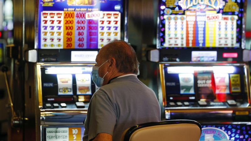 Man with a mask plays a slot machine