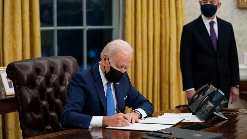 President Biden signs an order at his desk