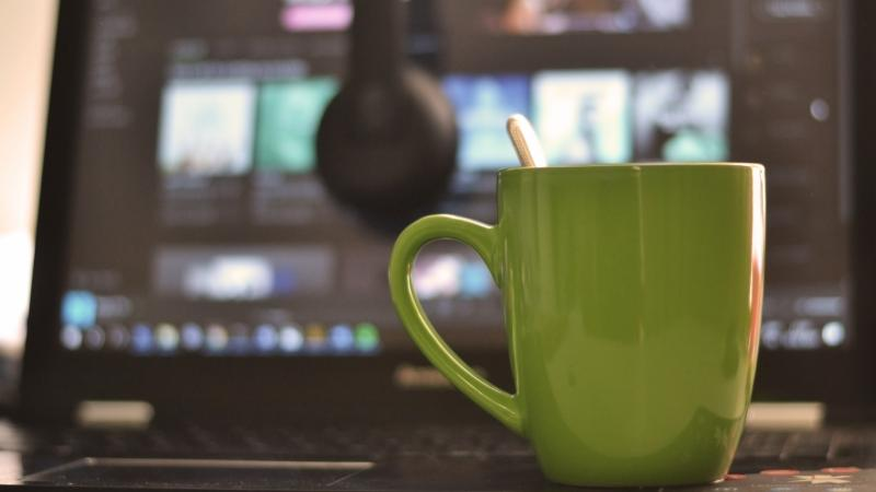 Coffee cup, a laptop computer and headphones