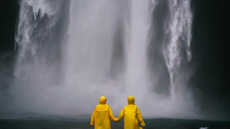 couple holding hands in front of waterfall