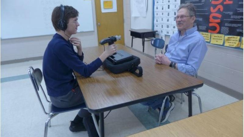 student interviewing man in a classroom