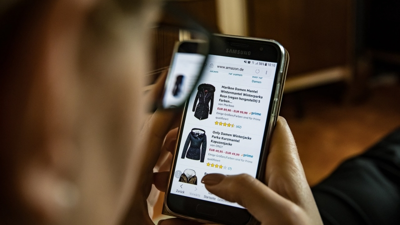 A person uses their cell phone to online shop