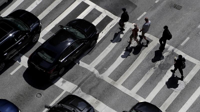 Pedestrians cross East Lombard Street in downtown Baltimore.