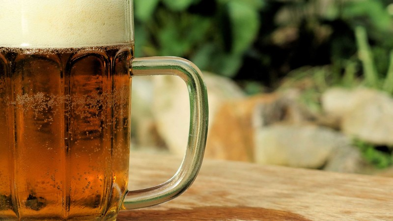 a mug of beer on a table in the sun