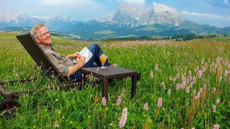 Rick Steves sits in a lounge chair with a map in hand in the middle of a lush green field with mountains in the distance.