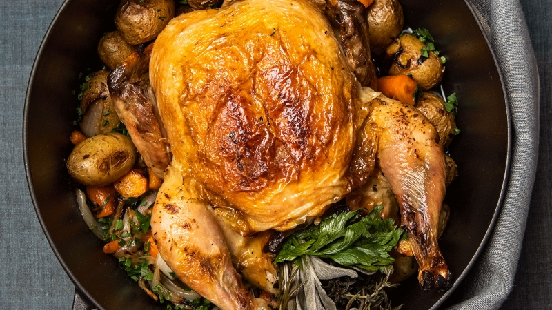 A person holds a roasted chicken in a Staub dutch oven