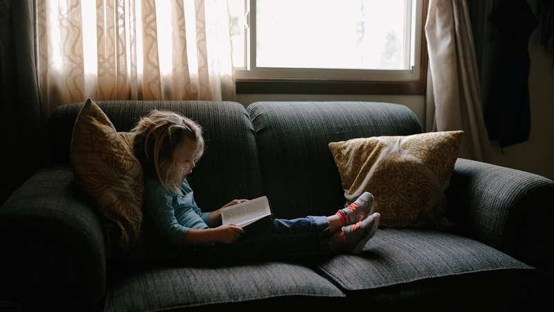 Child reading on couch.