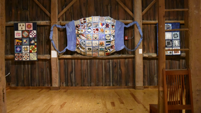 A giant mask created out of fabric squares is displayed on the barn-looking wall.