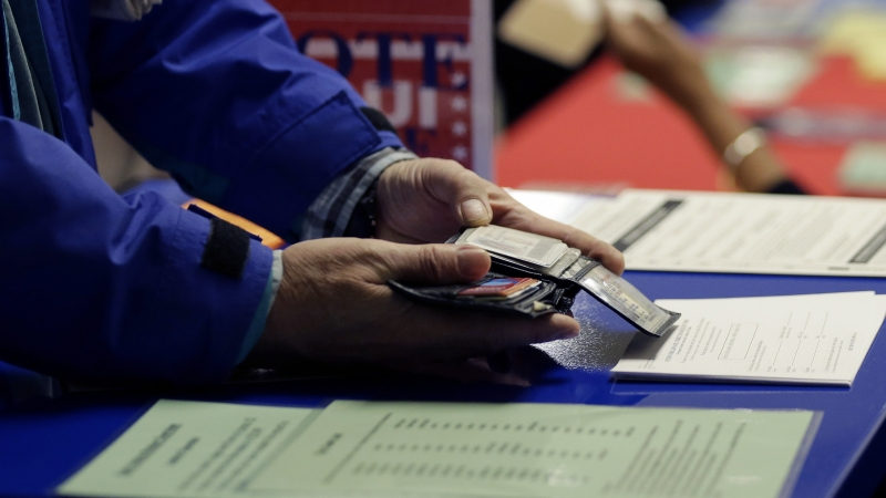 Person showing photo ID to vote