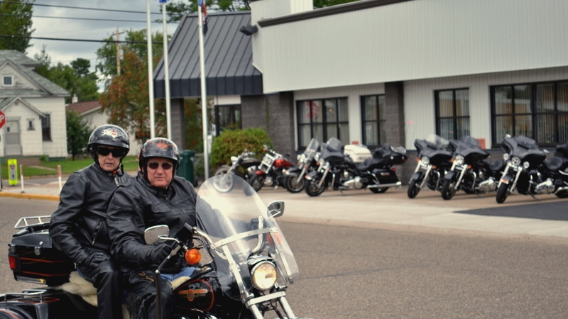 Two bikers riding a Harley in front of theHarley Soma Avenue Plant in Tomahawk.