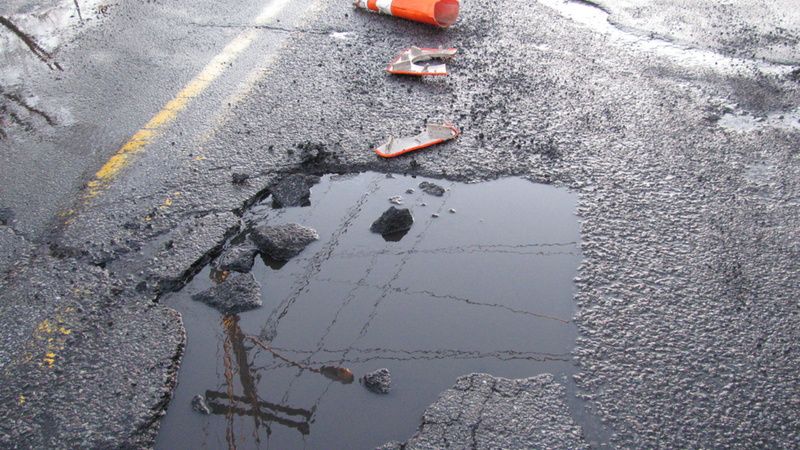a pothole in the middle of a wet road