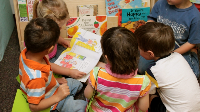 A group of children gathered around a book at child care