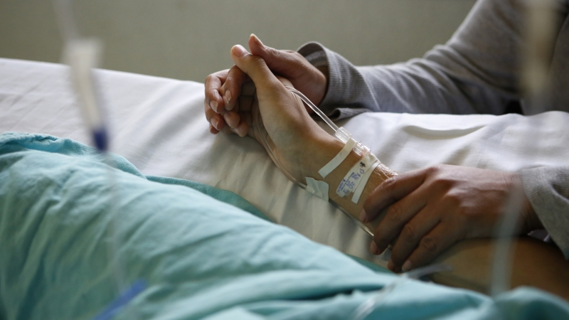 holding hands in hospital bed