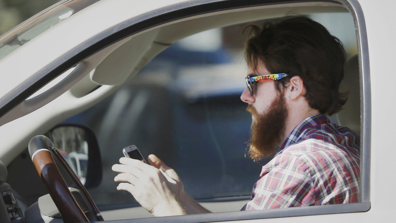 A man uses his cell phone as he drives through traffic in Dallas.